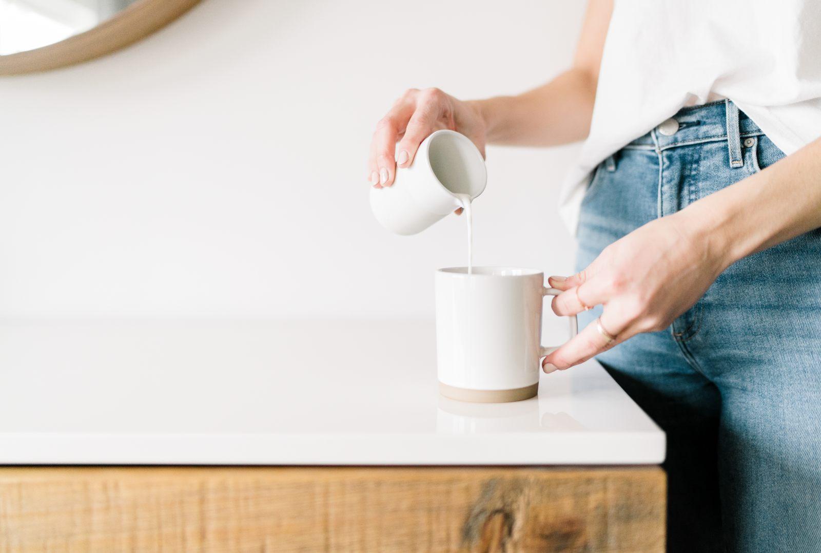 Woman pours milk into a cup