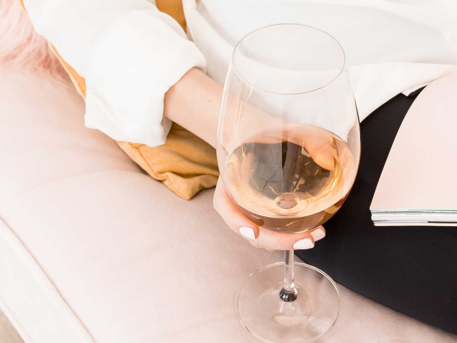 Woman's hand holding a wine glas while reading